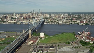 AX82_002 - 5K stock footage aerial video of Benjamin Franklin Bridge spanning the Delaware River near the Downtown Philadelphia skyline, Pennsylvania