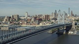 AX82_003E - 5K stock footage aerial video panning across Benjamin Franklin Bridge to reveal Downtown Philadelphia skyline, Pennsylvania