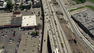 AX82_027 - 5K stock footage aerial video tilting from Interstate 95 with light traffic to reveal industrial buildings in North Philadelphia, Pennsylvania