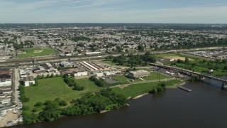 AX82_033 - 5K stock footage aerial video of Industrial buildings and factories around Tacony Palmyra Bridge, Philadelphia, Pennsylvania