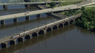 AX82_060 - 5K stock footage aerial video of a commuter train crossing the Morrisville-Trenton Railroad Bridge in Trenton, New Jersey