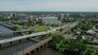 AX82_069 - 5K stock footage aerial video of Richard J. Hughes Justice Complex and office buildings near bridges spanning Delaware River, Trenton, New Jersey
