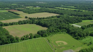AX82_083 - 5K stock footage aerial video flying over fields to approach a farm in Lawrenceville, New Jersey