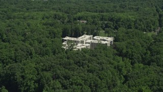 AX82_105 - 5K stock footage aerial video of an apartment complex partially hidden by trees in Princeton, New Jersey