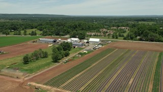 AX83_001 - 5K stock footage aerial video of a farm and crop field by a country road, Skillman, New Jersey