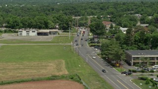 AX83_032 - 5K stock footage aerial video of light traffic on State Road beside a green field and abandoned building, Princeton, New Jersey