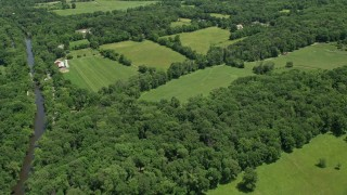 AX83_034 - 5K stock footage aerial video flying over farm fields with barns by the Millstone River in Belle Mead, New Jersey