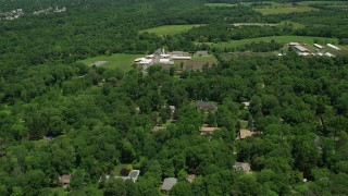 AX83_036 - 5K stock footage aerial video flying over rural homes to approach a farm with red barns in Princeton, New Jersey