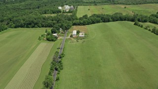 AX83_039 - 5K stock footage aerial video flying over fields and barns beside Canal Road in Franklin Park, New Jersey