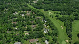 AX83_060 - 5K stock footage aerial video flying over suburban homes next to a golf course and power lines in Edison, New Jersey