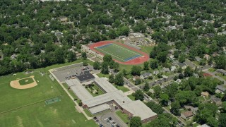 AX83_063 - 5K stock footage aerial video flying by school and sports fields in a suburban neighborhood, Westfield, New Jersey
