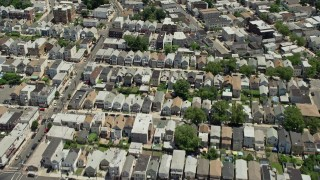 AX83_097 - 5K stock footage aerial video tilting from urban Newark homes to reveal and approach Manhattan skyline in the background, New Jersey & New York
