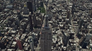 AX83_123 - 5K stock footage aerial video tilting to bird's eye of Empire State Building and skyscrapers, Midtown Manhattan, New York City