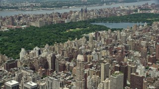 AX83_132 - 5K stock footage aerial video flying over Upper East Side apartment buildings to approach Central Park, New York City