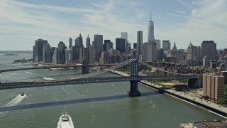 AX83_183E - 5K stock footage aerial video fly over Manhattan Bridge to approach Brooklyn Bridge and the Lower Manhattan skyline, New York City
