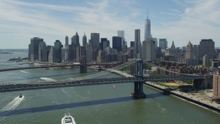 AX83_184 - 5K stock footage aerial video flying over Manhattan Bridge to approach Brooklyn Bridge and Lower Manhattan Skyline, New York City