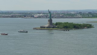 AX83_191 - 5K stock footage aerial video of Statue of Liberty and passing ferries in New York Harbor, New York City