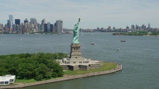 AX83_195 - 5K stock footage aerial video of Statue of Liberty with Brooklyn in the distance, New York