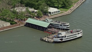 AX83_196 - 5K stock footage aerial video of crowds of tourists at the ferry dock on Liberty Island, New York