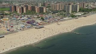 AX83_220E - 5K stock footage aerial video flying by Luna Park, Riegelmann Boardwalk, and Coney Island Beach sunbathers, Brooklyn, New York City