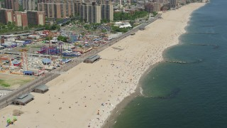 AX83_221 - 5K stock footage aerial video orbiting Luna Park rides and Coney Island Beach, Brooklyn, New York City
