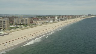 AX83_228 - 5K stock footage aerial video of beachfront apartment complexes and sunbathers at Rockaway Beach, New York
