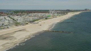 AX83_230 - 5K stock footage aerial video flying by beachfront condos and sunbathers, Far Rockaway, New York