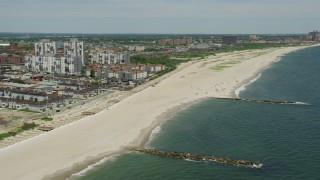AX83_231 - 5K stock footage aerial video flying by beachfront condo complexes and sunbathers at the beach in Far Rockaway, New York