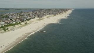 AX83_237 - 5K stock footage aerial video of beachgoers and beachfront neighborhoods, Long Beach, New York