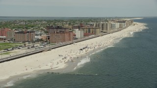 AX83_241 - 5K stock footage aerial video tilting to a Crowd of Sunbathers on the Beach, Long Beach, New York