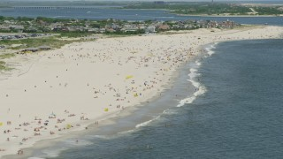 AX83_246 - 5K stock footage aerial video of a group of people on a Sandy Beach, Lido Beach, New York