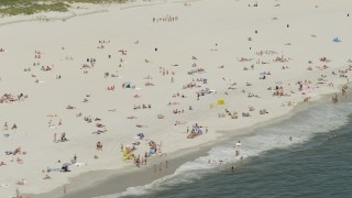 AX83_247 - 5K stock footage aerial video of a large Group of Beachgoers on a Sandy Beach, Lido Beach, New York