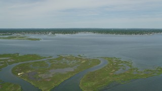 AX83_257 - 5K stock footage aerial video approaching Massapequa from small marshy islands in South Oyster Bay in New York