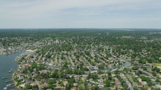 AX83_259 - 5K stock footage aerial video flying over suburban homes and a canal in Massapequa, New York