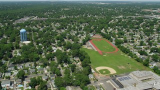AX83_261 - 5K stock footage aerial video flying over high school sports fields and approaching State Route 27 in Massapequa, New York