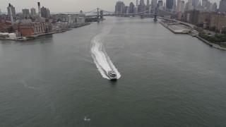 AX84_101 - 4K stock footage aerial video Flying over ferry, East River, Manhattan Bridge, Lower Manhattan skyline, New York
