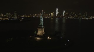 AX85_010 - 4K stock footage aerial video of the Statue of Liberty, Lower Manhattan skyline, New York, New York, night