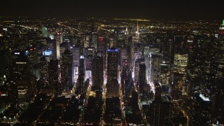 AX85_093 - 4K stock footage aerial video Skyscrapers in Midtown Manhattan, streets, New York, New York, night