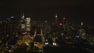 AX85_113 - 4K stock footage aerial video Flying by Midtown Manhattan, revealing West Side Yard, New York, New York, night