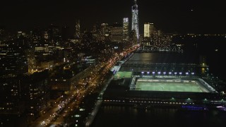 AX85_117 - 4K stock footage aerial video Tilt up from piers, Chelsea, Lower Manhattan, New York, New York, night