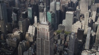 AX87_112 - 4K stock footage aerial video Flying by top of Empire State Building, Midtown Manhattan skyscrapers, New York