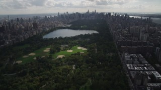 AX87_125 - 4K stock footage aerial video Flying away from Central Park, seen from Harlem, New York, New York