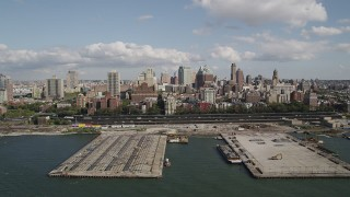 AX88_002 - 4K stock footage aerial video of flying by piers and skyscrapers, seen from East River, Brooklyn, New York