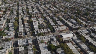 AX88_032 - 4K stock footage aerial video of flying over row houses, tilt up to wider view, Brooklyn, New York