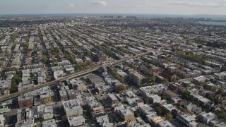 AX88_033 - 4K stock footage aerial video of flying over row houses, tilt to railroad tracks, Brooklyn, New York