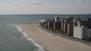AX88_051 - 4K stock footage aerial video of flying by Coney Island Beach and apartment buildings in Brooklyn, New York, New York