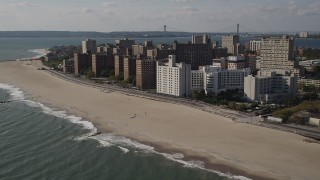 AX88_063 - 4K stock footage aerial video of passing by Coney Island Beach and apartment buildings, Brooklyn, New York