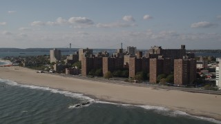 AX88_064 - 4K stock footage aerial video of beachfront apartment buildings by Coney Island Beach, Brooklyn, New York