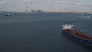 AX88_089 - 4K stock footage aerial video tilt from water to reveal oil tanker sailing New York Harbor and Lower Manhattan skyline, New York, New York