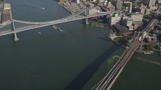 AX88_121 - 4K stock footage aerial video pan from Manhattan Bridge to famous Brooklyn Bridge, East River, New York, New York